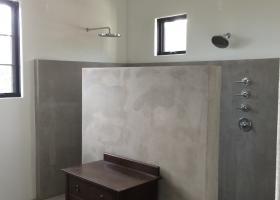 Concrete showers and floors. Rain head, handheld plumbing fixtures.