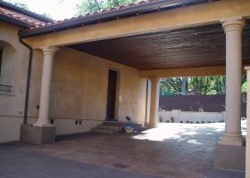 Covered car portico with stamped colored concrete.