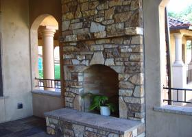 Outdoor living space featuring stone fireplace.