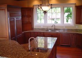 Granite counters, wood panel doors for appliances, raised bar island.